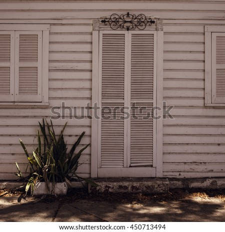 old wooden white door and windows on a white wooden wall with a small plan growing close to it in the autumn. Miami. Bahia Honda Park. Florida. USA. - stock photo
