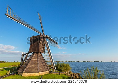 Old wooden windmill alongside a lake in the Dutch province of Friesland - stock photo
