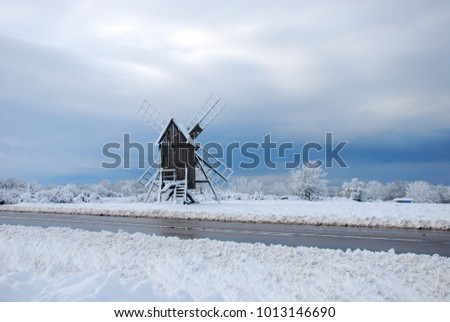 Old wooden windmill by roadside in a winter landscape at the swedish island Oland