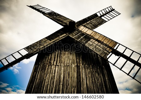 Old wooden windmill in the dark tones - stock photo