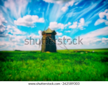 Old wooden windmill in the summer blue sky and green land, blurred background