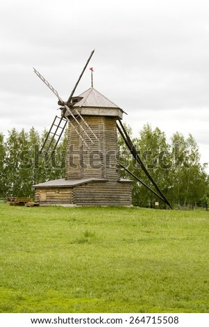 Old wooden windmill near the forest and meadow with green grass - stock photo