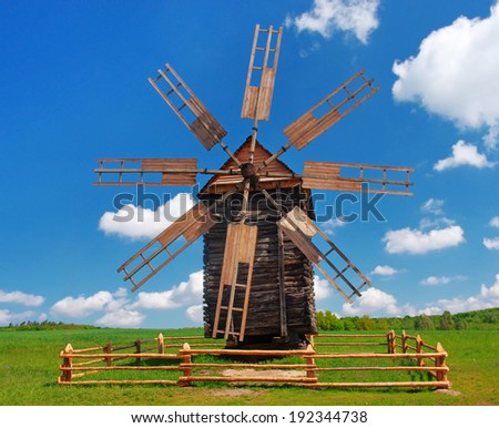 Old wooden windmill on  the background of blue sky