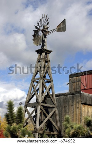 Old Wooden Windmill with Clouds on teh Background - stock photo