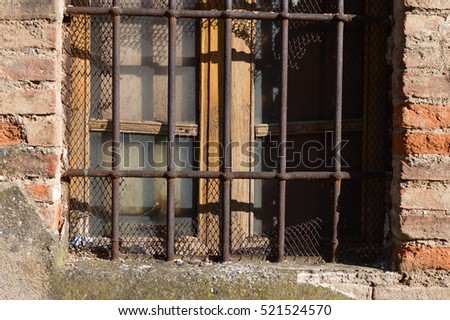 Old wooden window with dirty glasses and antique rusty grate with a torn net. Red brick wall and cement with green moss. Illuminated by sun.