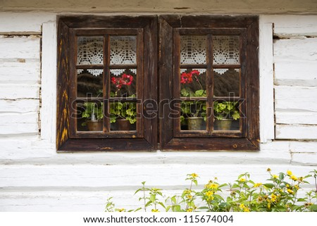 Old wooden window with flowers and curtain