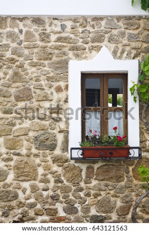 old wooden window with flowers on stone wall