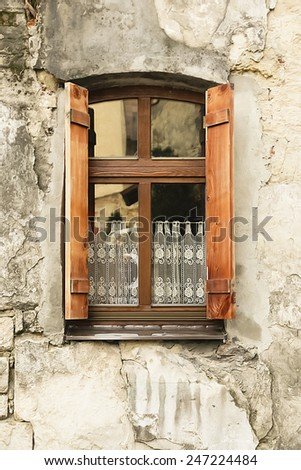 old wooden window with shutters and lace curtains. - stock photo