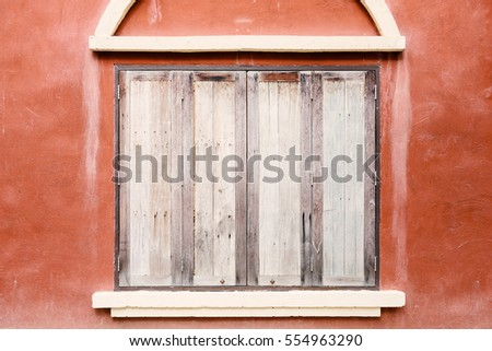 old wooden windows on orange concrete wall