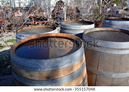 old wooden wine barrels in the backyard of a tavern after the rain - stock photo