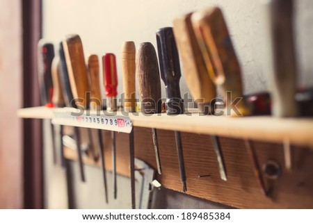 Old woodworking tools on wall, retro tinted - stock photo