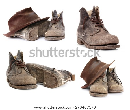 Old work boots and battered hat.  Collection isolated on white. - stock photo
