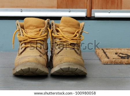 Old work boots on a porch. - stock photo