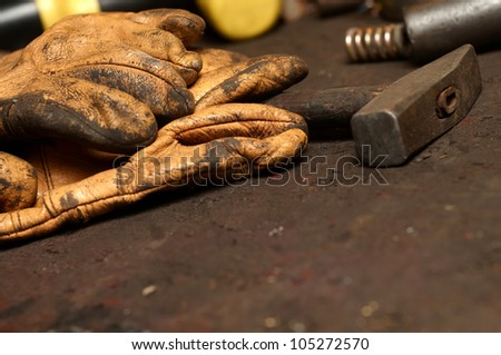 Old Work Gloves and hammer in workshop - stock photo