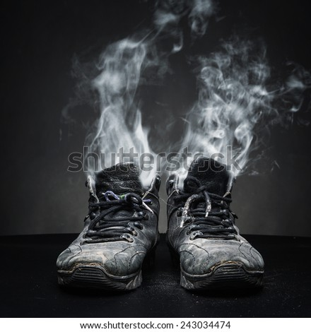 Old work shoes in smoke - stock photo