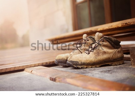 Old worker boots left on unfinished patio wooden flooring - stock photo