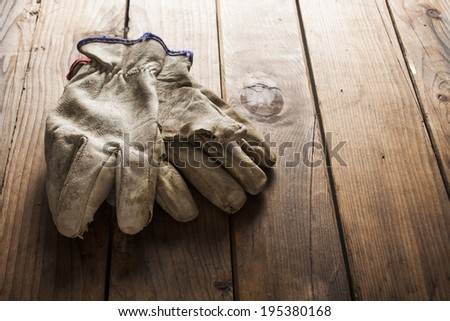 Old working gloves over wooden table, construction tools - stock photo