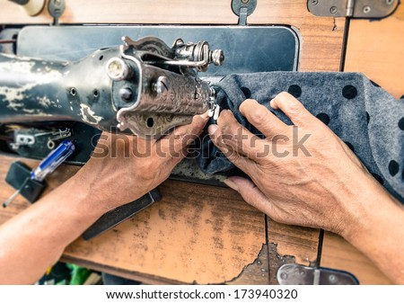 Old working hands at sewing machine - stock photo