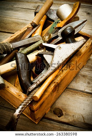 Old working tools. Old working tools (drill, saw, axe and others) in a box on a wooden background. - stock photo