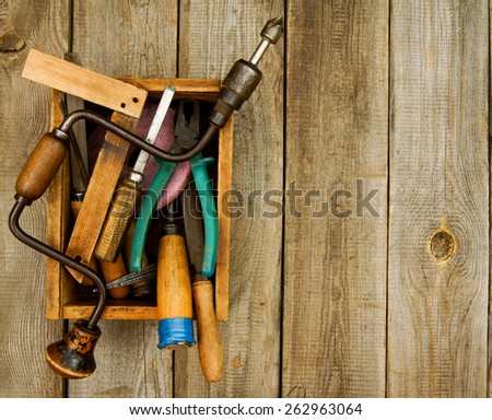 Old working tools. Old working tools (saw, axe, plane and others) in a box on a wooden background. - stock photo