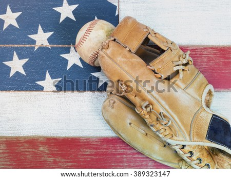Old worn baseball mitt and baseball on faded wooden boards painted red, white and blue with flag pattern.