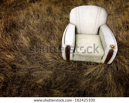 Old worn chair sitting abandoned in tall grass and weeds - stock photo