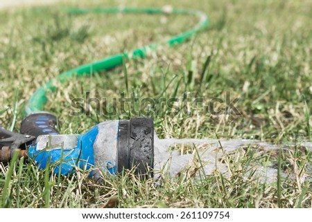 Old worn garden hose spray gun running water on green and dry grass. Abandoned sprayer left on a thirsty lawn spraying a stream of water. Close up low angle view.  - stock photo