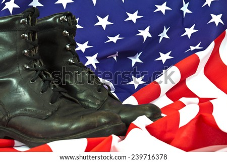Old worn leather military boots on American flag - stock photo