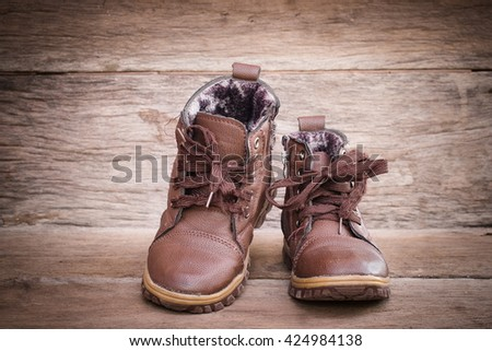 Old worn out brown shoes, leather shoes, zipper shoes, over the brown background - stock photo