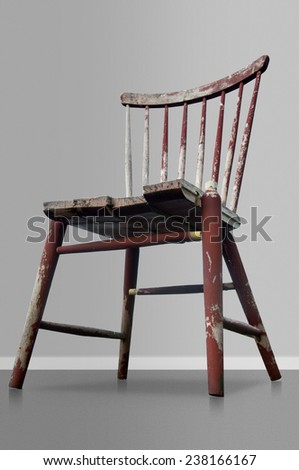 Old worn red wooden chair on gray background