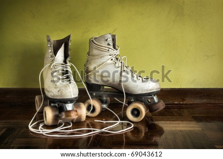 Old worn roller skates with big shoe-laces on a yellow wall background - stock photo