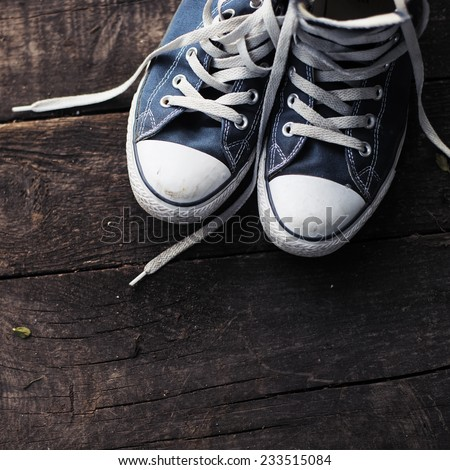 Old worn sneakers on a background of boards - stock photo