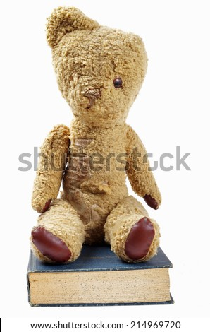 old worn teddy bear and old blue book  - stock photo