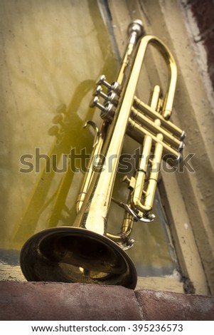Old worn trumpet stands alone against a grungy wall