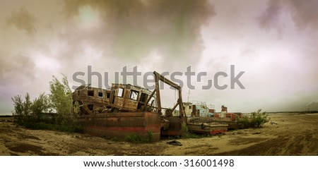 Old wrecked boat on the coast. Autumn sky background. - stock photo