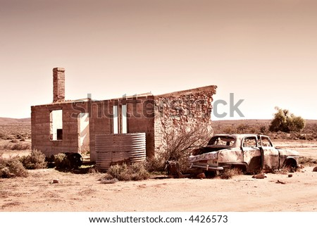 old wrecked car and ruins in the desert