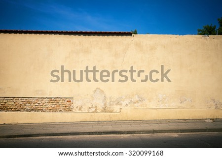 Old yellow brick and plaster wall with lots of copy space also showing sidewalk and sky - stock photo