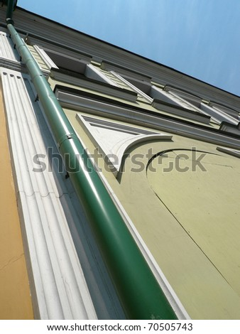 old yellow building with green storm-down pipe - stock photo
