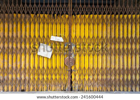 Old yellow folding door with holder - stock photo