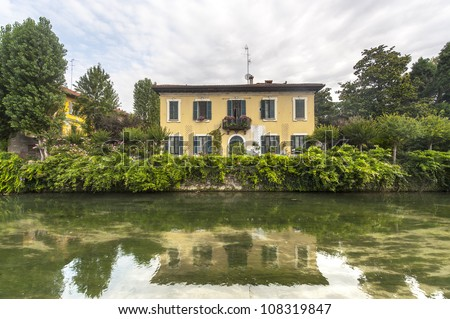 Old yellow house with garden on the Martesana canal near Crescenzago (Milan, Lombardy, Italy)