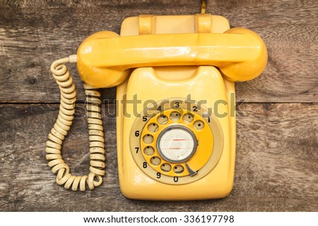 Old yellow phone with dust and scratches on wooden retro floor. - stock photo
