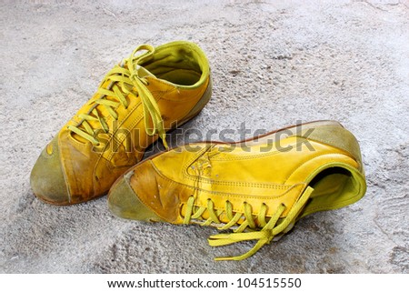 old yellow shoes on concrete - stock photo
