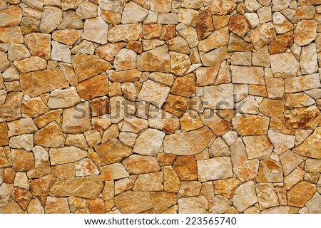 Old yellow wall, built of rough brick - stock photo