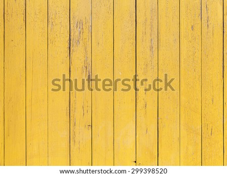 Old yellow wooden wall with cracked paint layer, detailed background photo texture - stock photo