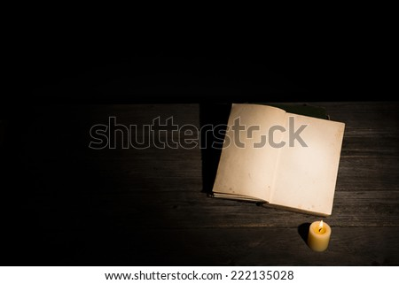 Old yellowed, blank book and a burning candle in a dark room - stock photo