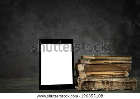 Old yellowed books and self-designed tablet computer with blank display