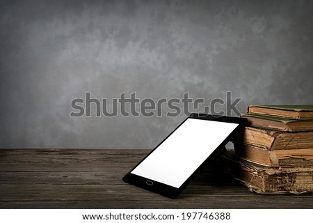 Old yellowed books with self-designed tablet computer - stock photo
