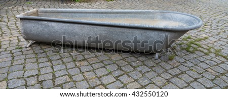 old zinc bathtub in paved courtyard - stock photo