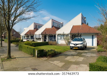 OLDENZAAL, NETHERLANDS - MARCH 23, 2015: Modern row of identical detached houses with front garden and own parking lot