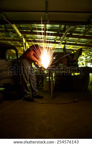 older adult male welding in machine shop with sparks flying